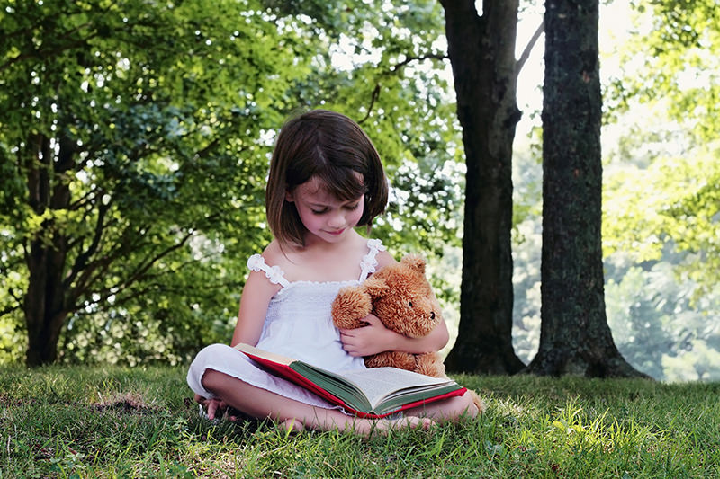 girl reading outstide with her bear