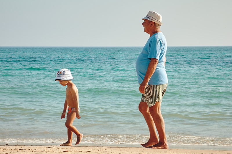grandfather and grandson walking on beach