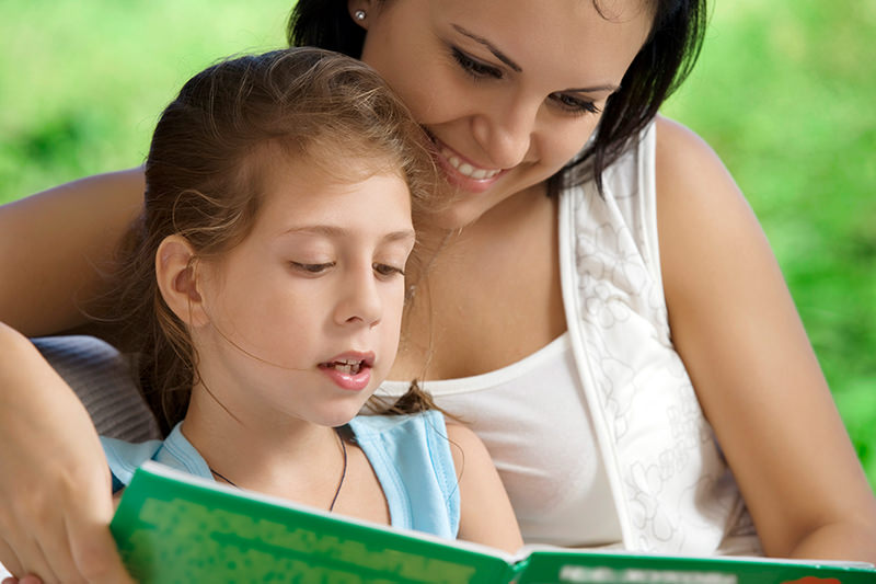 mother and young girl reading together