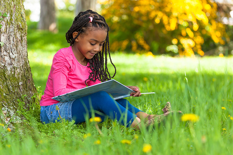 young girl reading outside under a tree